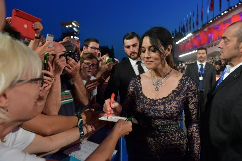 Italian Actress Monica Bellucci takes a moment to sgn an autograph on the Red Carpet at the 73rd Venice International Film Festival. (Photo courtesy of ASAC Images/Biennale Cinema)
