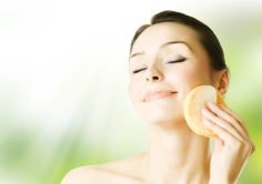 A woman cleansing her face with a sponge