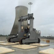 A HI-STORM UMAX Facility with a Transporter and a Cooling Tower in the Background