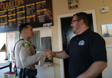 An Imperial County Sheriff's Deputy Greets Jerry Cerros propietor of Los Cerritos