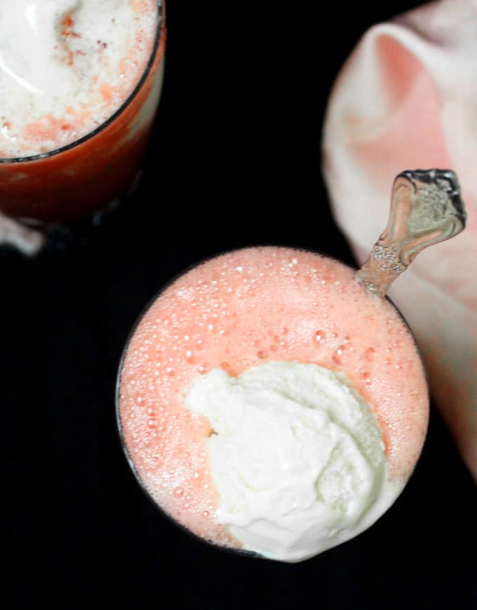 Top view of a frothy glass of watermelon smoothie with a dollop of ice cream and a pink napkin on the side.