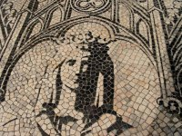 Photo of a mosaic showing the crowned woman from head to shoulders. The mosaic uses just black and white colors.