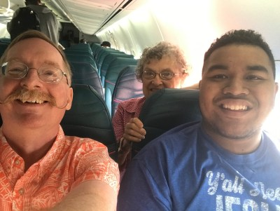 Pastor Eric, Sue Smith, and John Narruhn aboard an airplane (on a trip of Synod delegates earlier in the month).