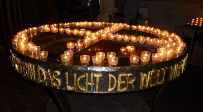 "Photo shows a circle of small candles in glasses arranged in a circle with a cross through the center, with words in German around the edge meaning ""light of the world."""