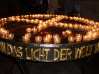 """Photo shows a circle of small candles in glasses arranged in a circle with a cross through the center, with words in German around the edge meaning """"light of the world."""""""