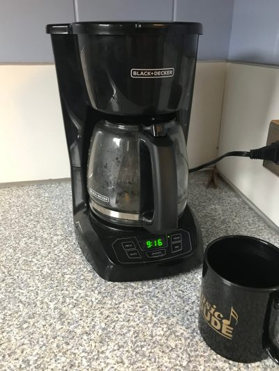 Photo of a coffee pot with coffee brewing.