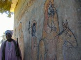 Photo: Paul Perry, a local standing beside a painting of the Holy Family's journey to Egypt at the monastery outside the town of Dayrut Al–Sharif.