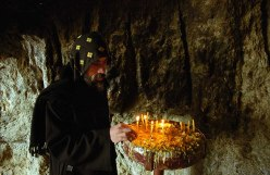 Photo: Norbert Schiller, a monk from Monastery of Dayr Durunka lights a candle at the entrance to the cave where apparitions of Virgin Mary have appeared in recen years.