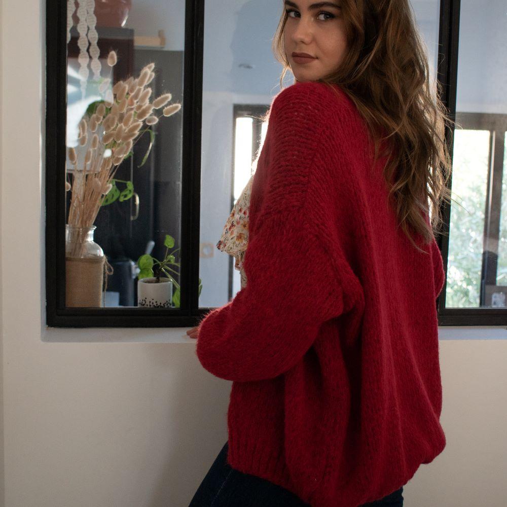 femme montrant un gilet long grosse maille rouge de dos