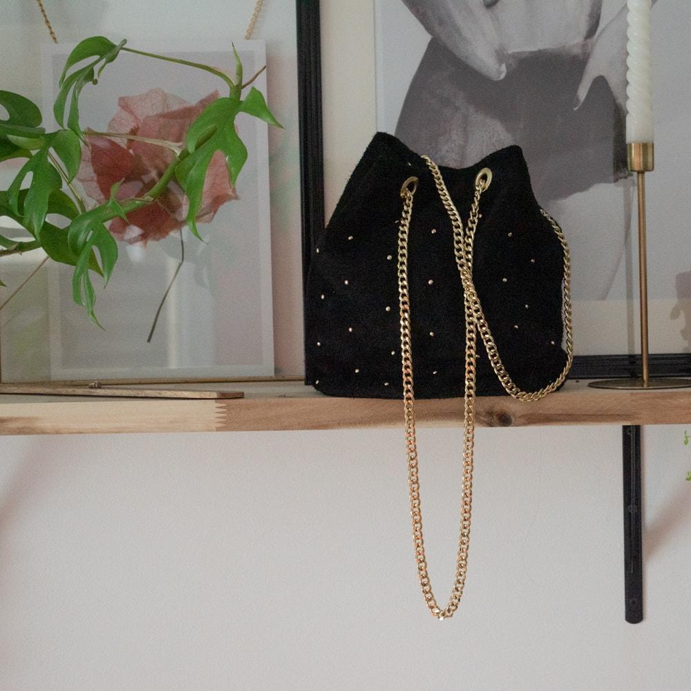 sac à main en cuir noir posé sur une étagère