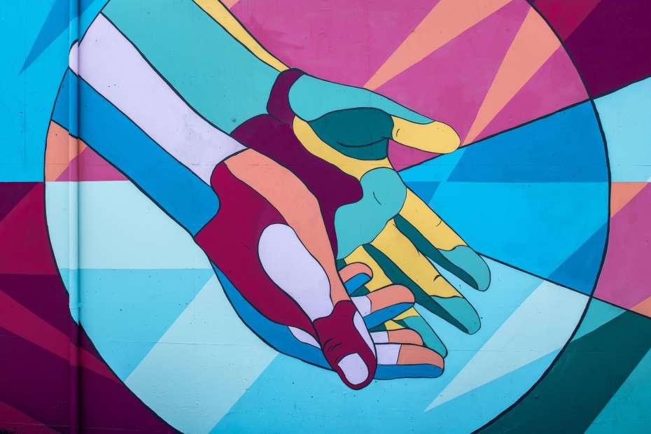illustration of colourful open hands. Photo by Tim Mossholder on Unsplash