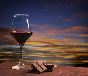 Wine glass and chocolate with colorful sunset