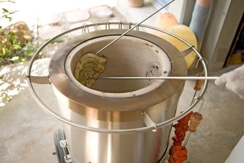 naan cooking in a tandoor oven