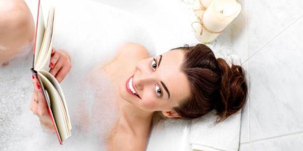 mujer en la tina leyendo un libro, sonriendo. disfrutando un baño