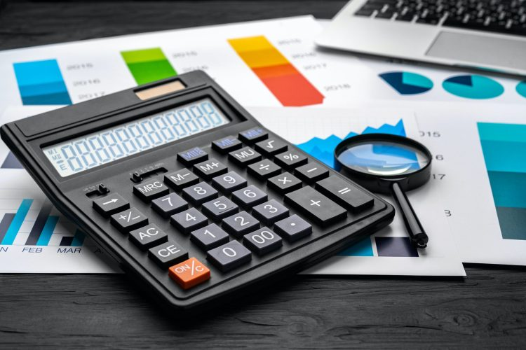 Business graphs paper and calculator on table