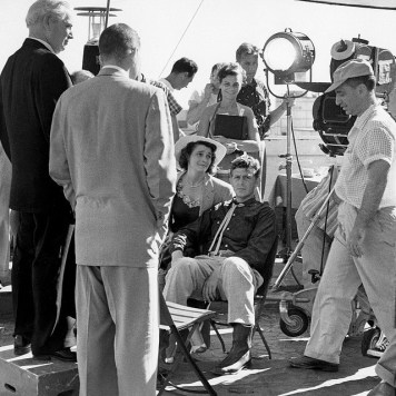 Patricia-Neal-and-Andy-Griffith-sitting-as-director-Elia-Kazan-stands-in-front-of-camera-on-the-set-