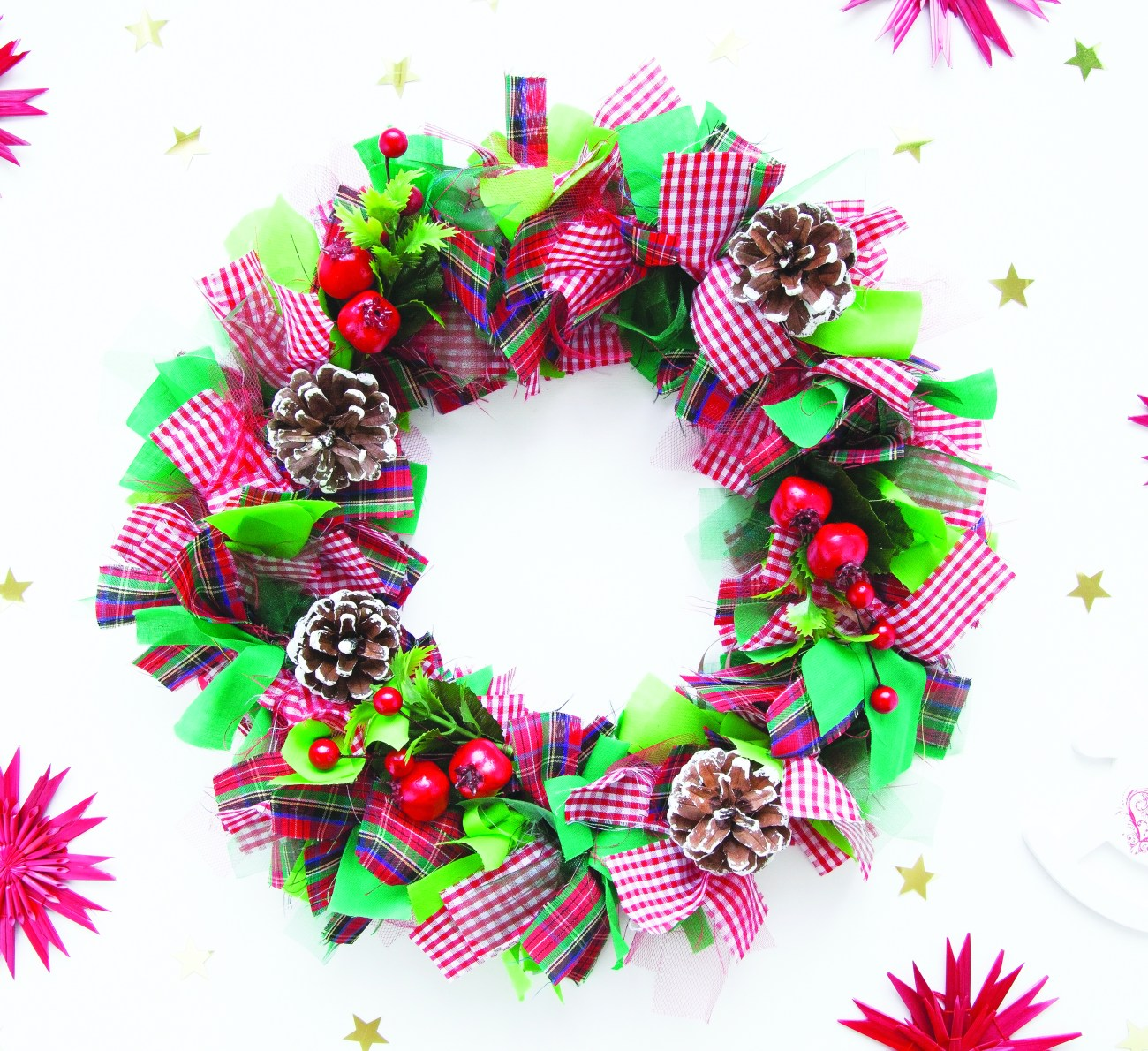 Christmas wreath made of colorful ribbons, cones, candy canes, poinsettia petals and artificial holly berries. White background.