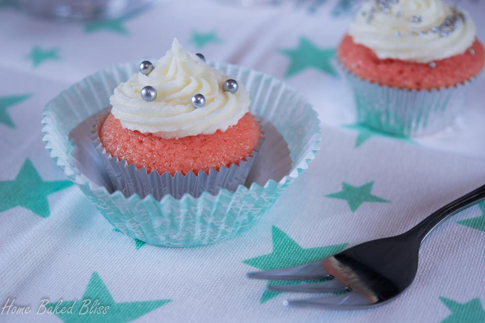 A mini sparkling wine cupcake inside a large muffin liner sitting next to a dessert fork