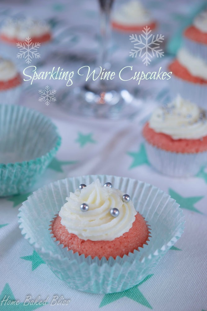 Mini sparkling wine cupcake decorated with white icing and sugar pearls on a white and turquoise tablecloth.