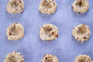 Thumbprint cookies laid out on a cookie sheet.