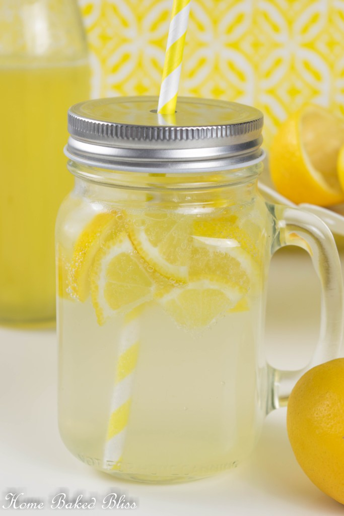 A mason jar filled with lemonade, ice cubes and a yellow straw.