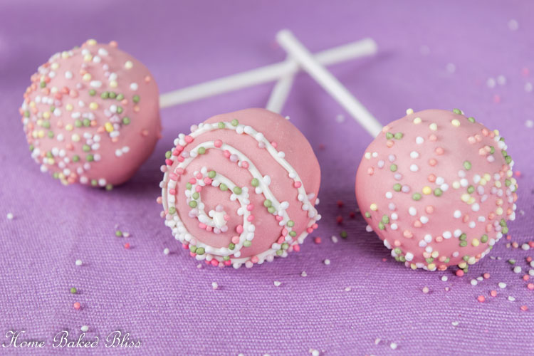 Chocolate cake pops with pink coating and colorful sprinkles on a purple background