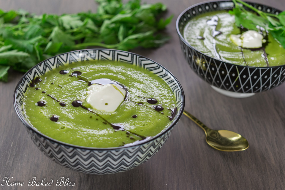 Two bowls of zucchini soup garnished with sour cream and pumpkin seed oil.