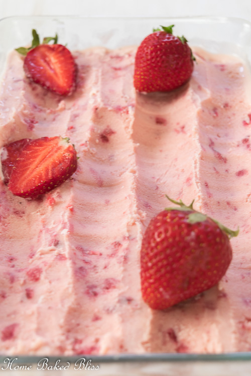 Strawberry Ice Cream in a glass pan garnished with fresh strawberries