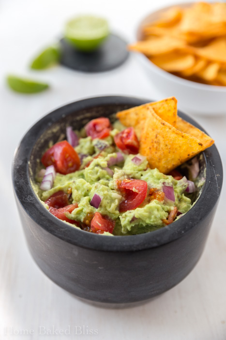 classic guacamole with tomatoes, red onions and chips
