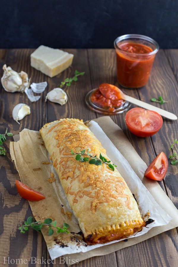 Cheesy calzone on parchment paper garnished with fresh oregano.