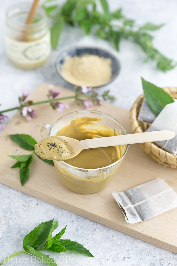 Green tea clay mask in a cup with a wooden spoon resting on top.
