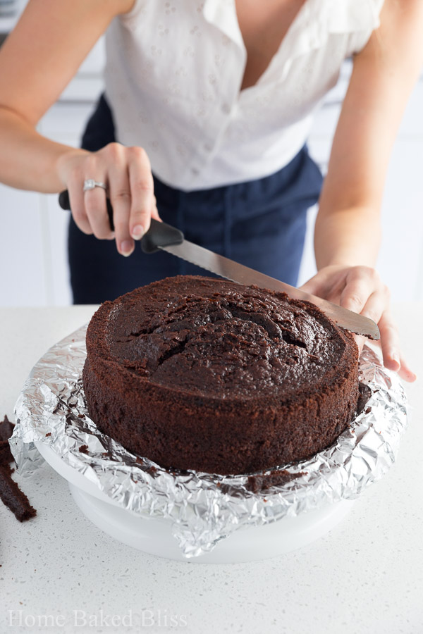 A woman cutting off the top of a chocolate cake to even it out.