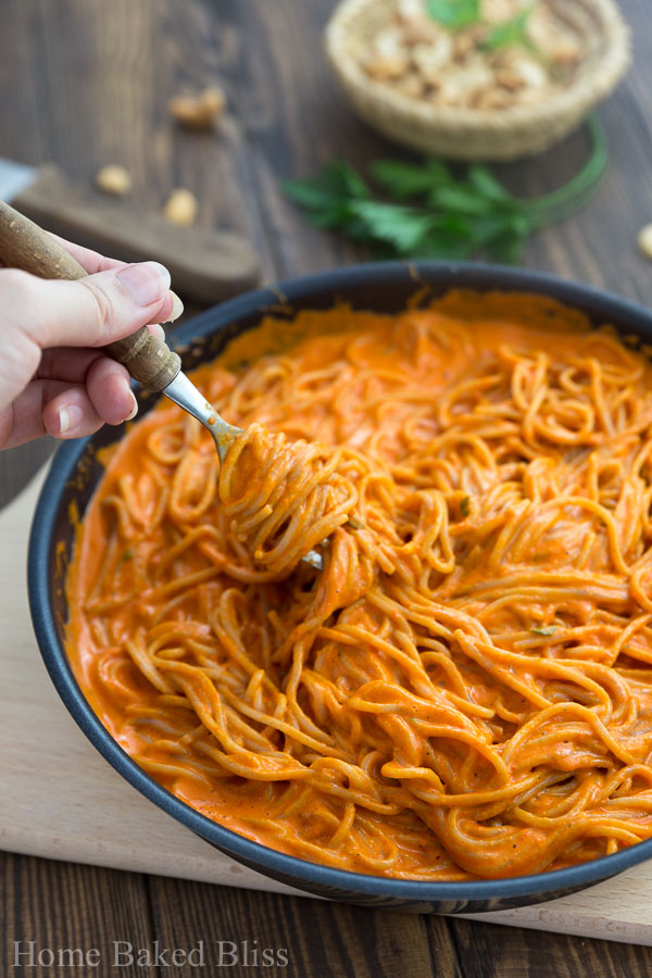 A fork digging into the thick and creamy roasted red bell pepper sauce with noodles.