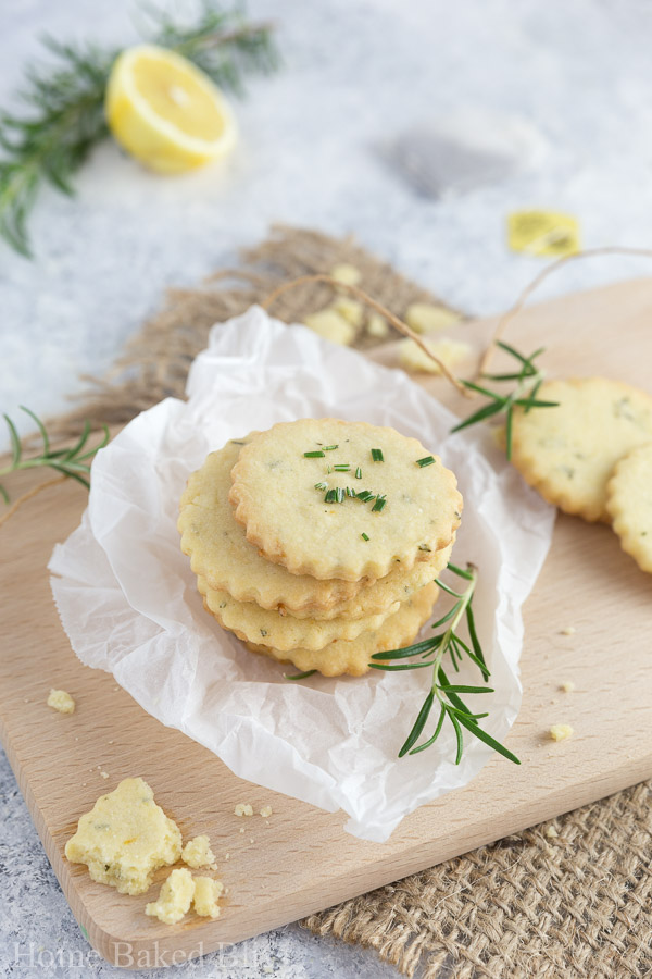 Rosemary lemon cookies stacked in a pile, sprinkled with fresh rosemary sitting on a cutting board.