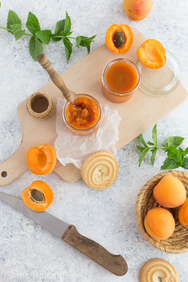 Two jars of homemade apricot jam on a wooden board.