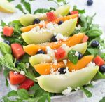 A melon salad on a bed of arugula, topped off with feta cheese and blueberries on a white plate.