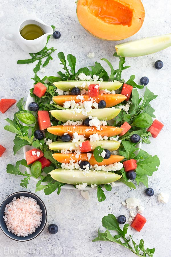A melon salad with feta cheese, arugula, blueberries, watermelon on a white plate.