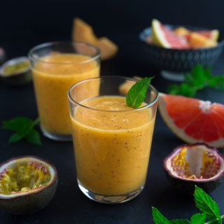 Two glasses of tropical smoothie garnished with a mint leaf beside various fruits