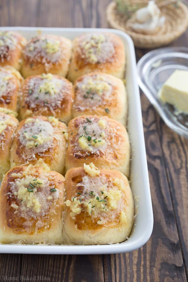 A closeup of the garlic parmesan dinner rolls inside a white casserole pan.