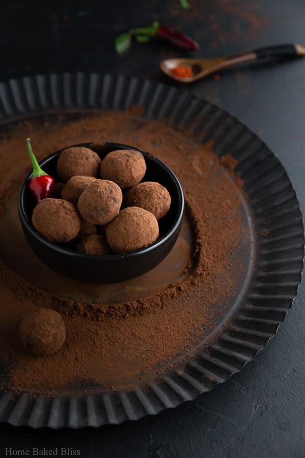 Spicy chili truffles inside a dark brown bowl.