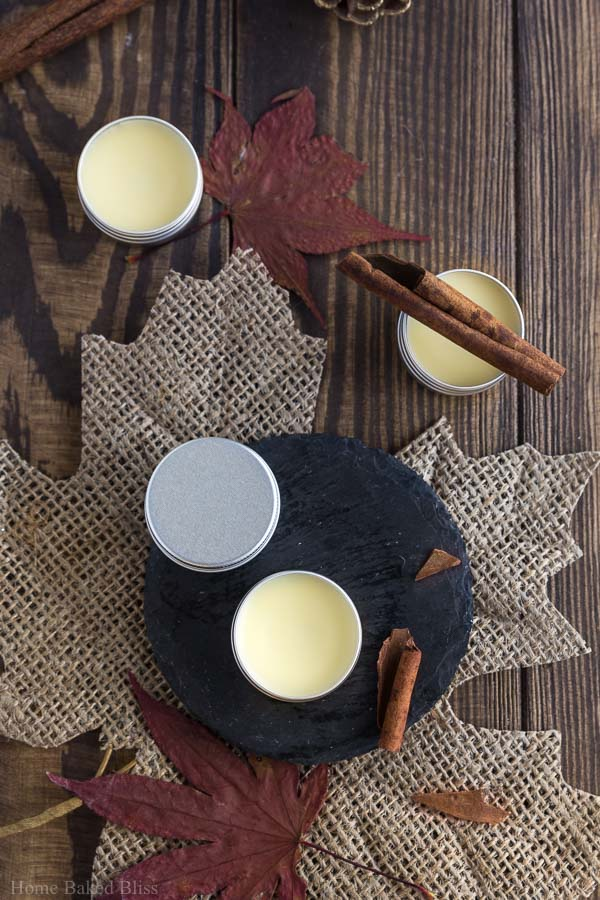 Cinnamon Cocoa Lip Balm in small metal containers on a wooden background.