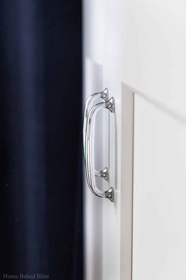 Silver handles with a blue curtain in the background