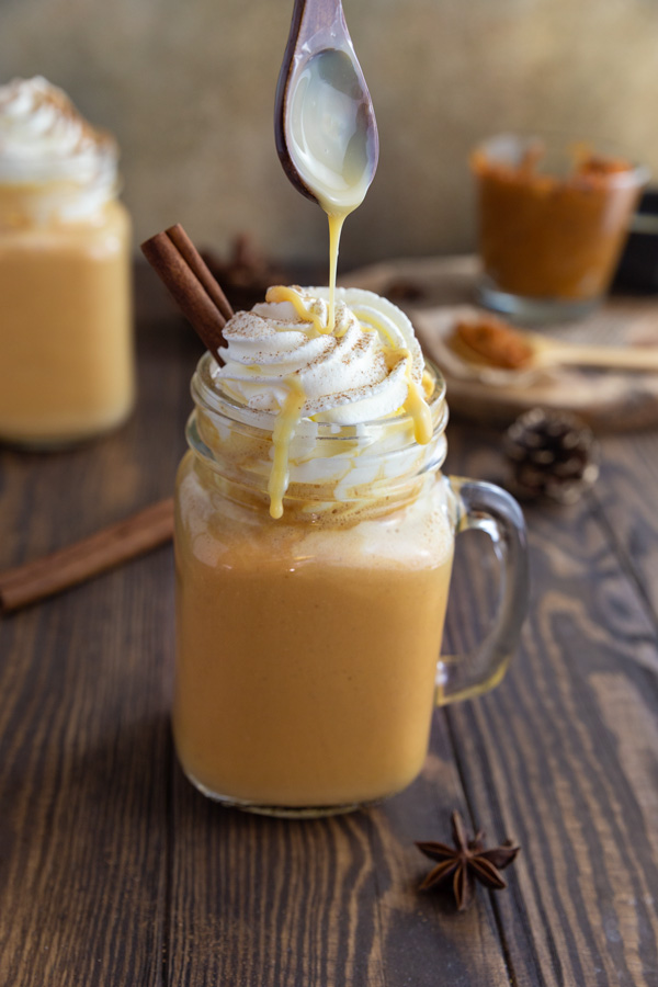 Drizzling condensed milk onto a pumpkin spice latte in a mason jar.