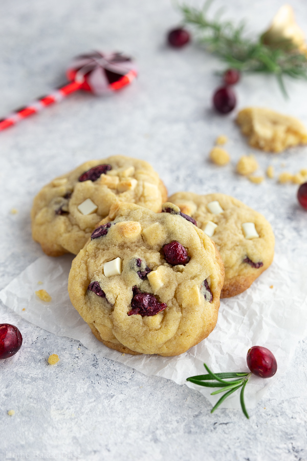 Cranberry white chocolate chip cookies on a white surface.