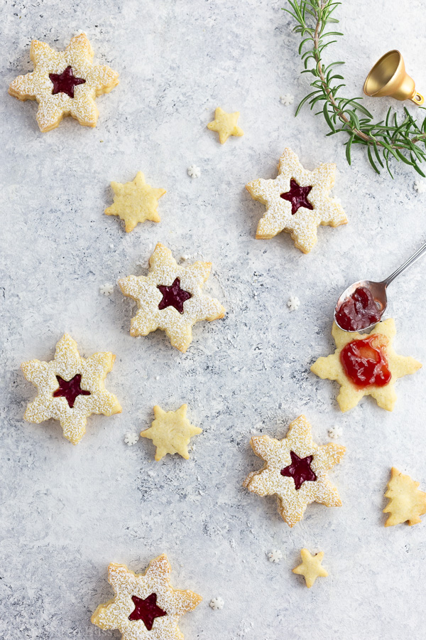 Jam filled Linzer cookies on a white background.