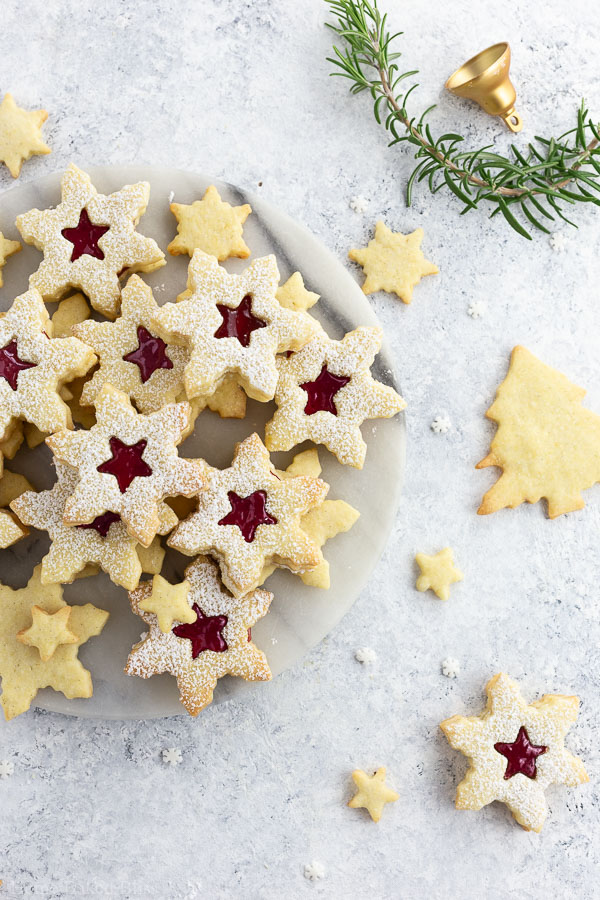 A marble plate of sugar dusted Linzer cookies.