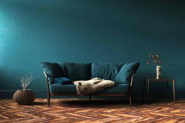 Mavimsi yeşil renkli bir kanepe ve zikzak desenli halı ile mavi temalı bir oturma odası
