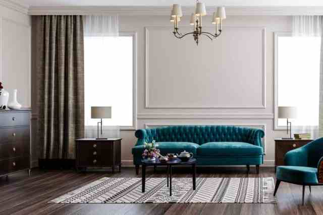 Beyaz boyalı duvar, ahşap zemin ve açık mavi renkli bir kanepe ile havalı rustik temalı bir oturma odası