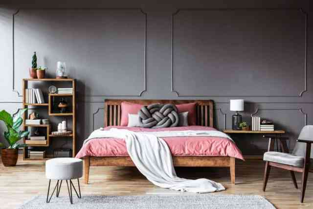 Pembe nevresim takımı ve oturma odasının her yerinde koyu ahşap mobilyalar ile koyu temalı klasik tarz yatak odası