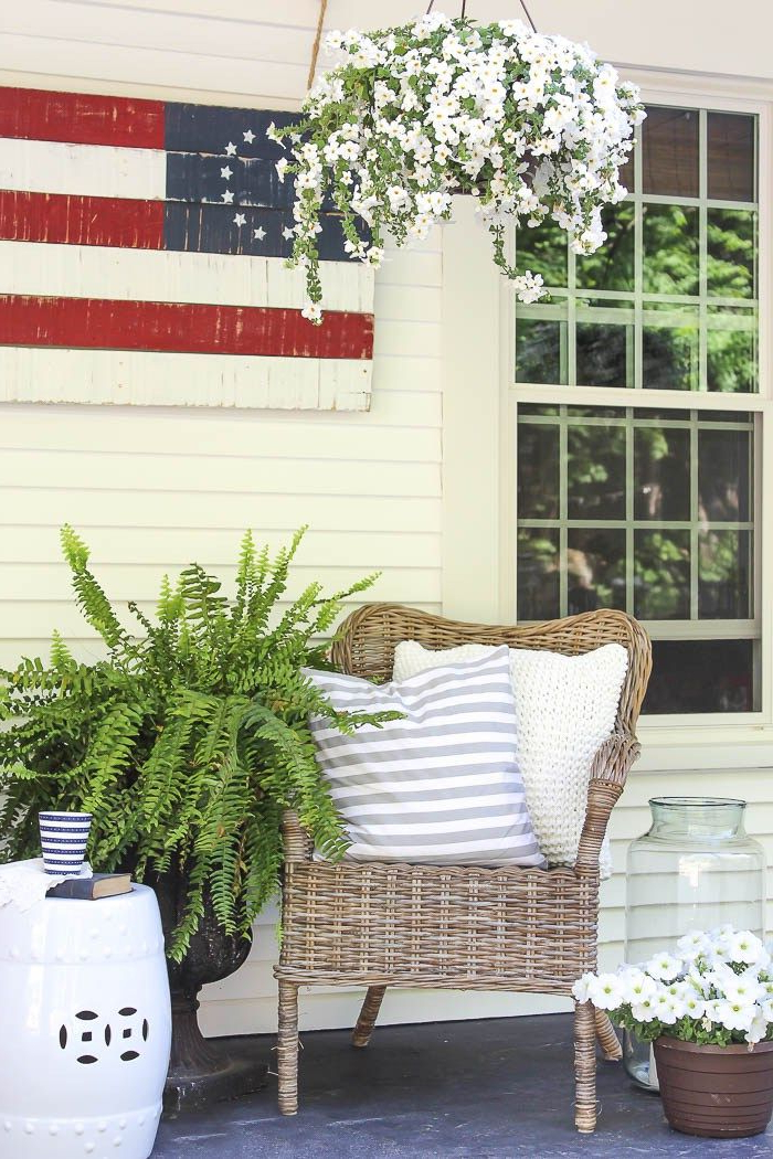 A Charming Farmhouse Covered Porch Is Decorated For Summer